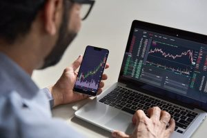 Business man trader investor analyst using mobile phone Bitcoin Trader app analytics for cryptocurrency financial market analysis.